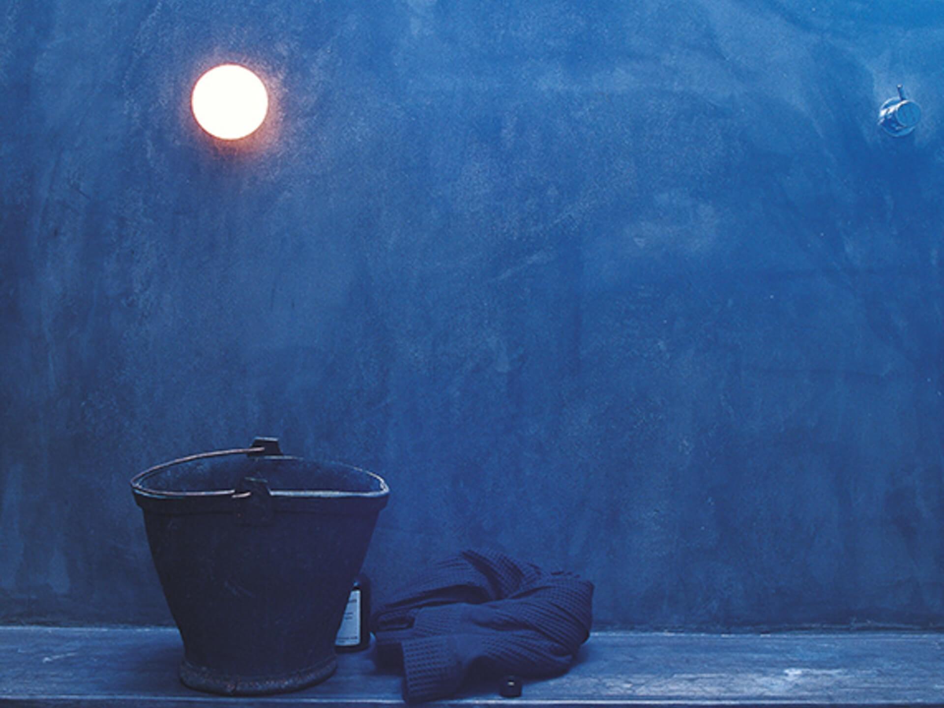 Miljøbilde vegglampe til bad. Glo ball mini fra Flos. Blått bad med lampe på vegg.