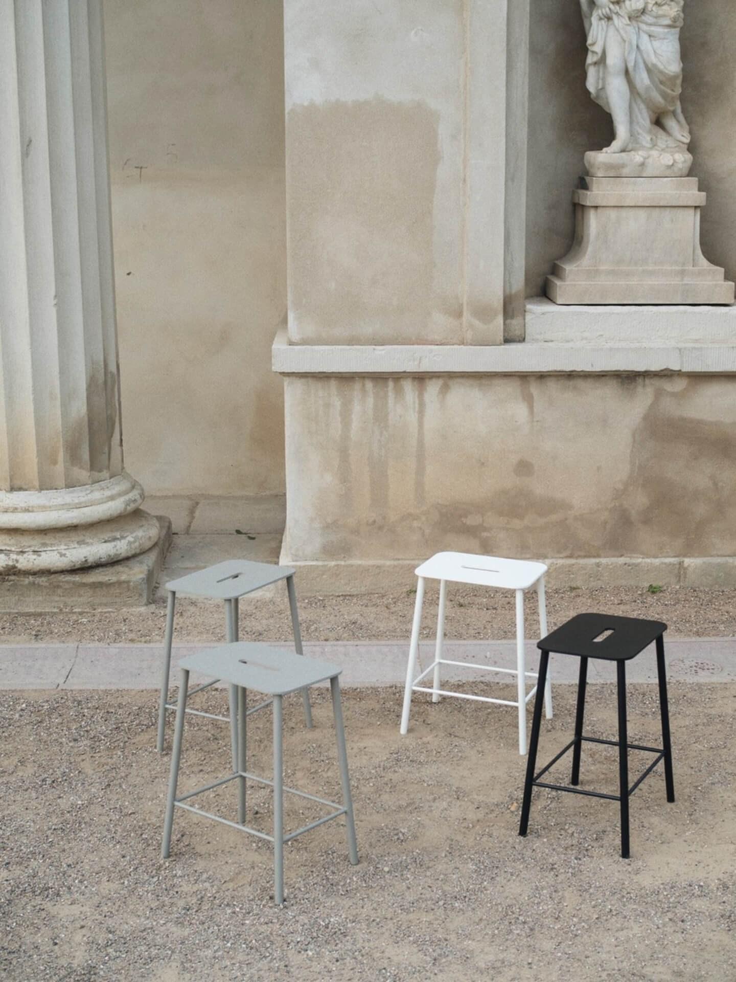 Miljøbilde krakk til bad i stål. Nærbilde av Adam stool i sort, hvit og grå fra Frama i beige omgivelser utendørs.