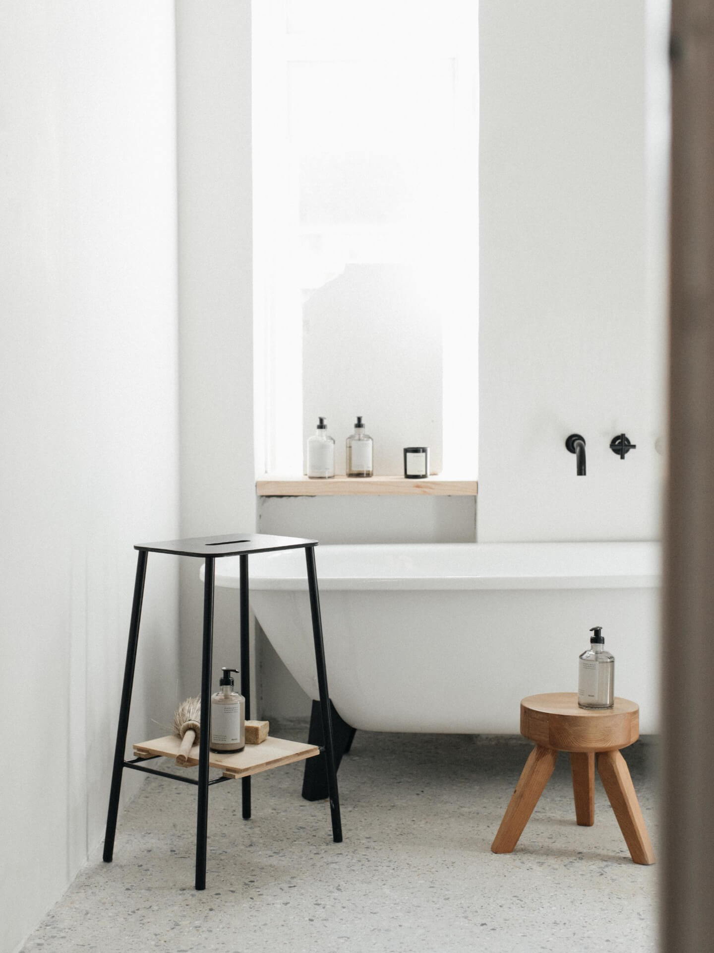 Miljøbilde Frama bad. Sement på gulv med detaljer i eik, krakk til bad, håndsåpe og sort armatur.