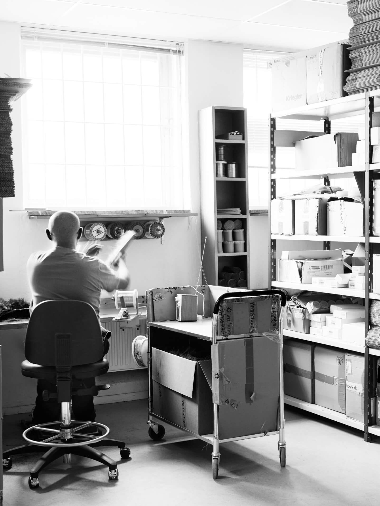 Miljøbilde av badebørster og skrubber fra Iris Hantverk. Bilde av mann bakfra på børstebindingsfabrikken.