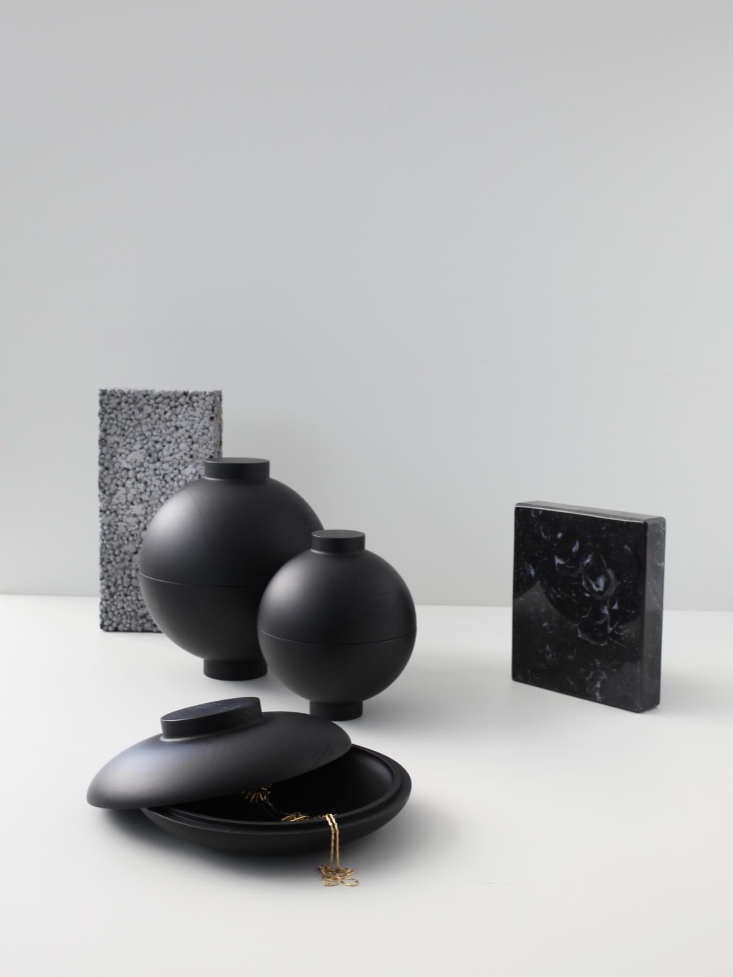 Miljøbilde Wooden Sphere og Wooden Galaxy fra Kristina Dam. Oppbevaringsboks i sortmalt tre. Samling med grå bakgrunn.