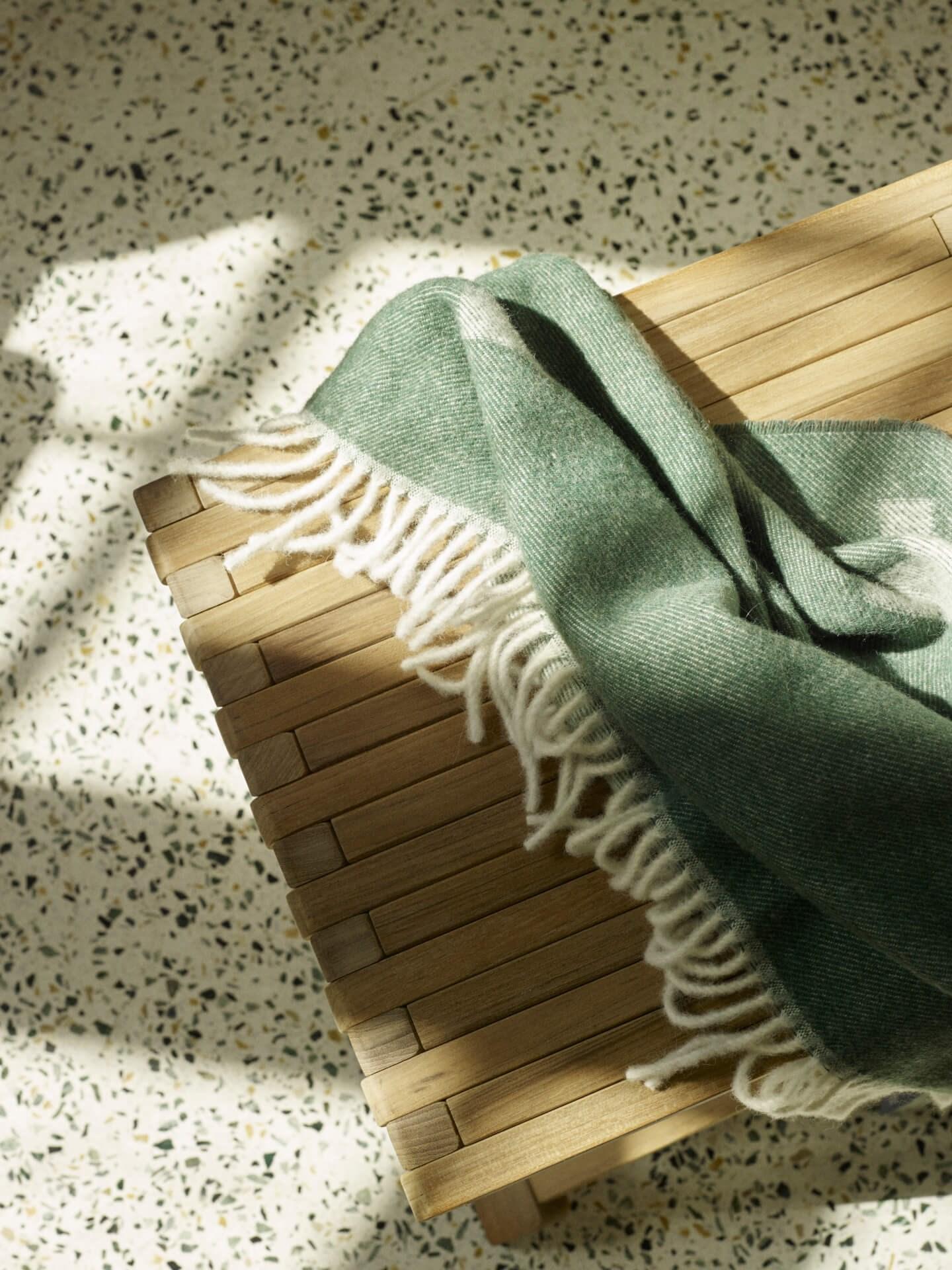 Miljøbilde krakk til bad. Fionia stool fra Skagerak på gulv i terrazzo og grønt teppe. Nærbilde ovenfra.