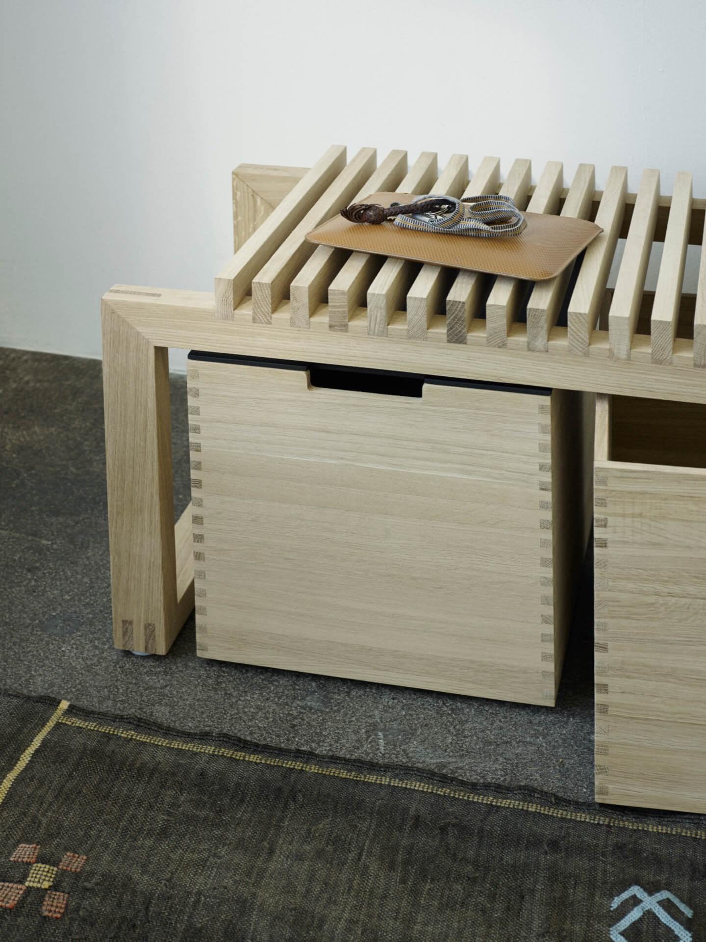 Oppbevaringsboks til bad og benk til bad. Cutter box og Cutter bench fra Skagerak. Plassert på mørkt gulv. Nærbilde.