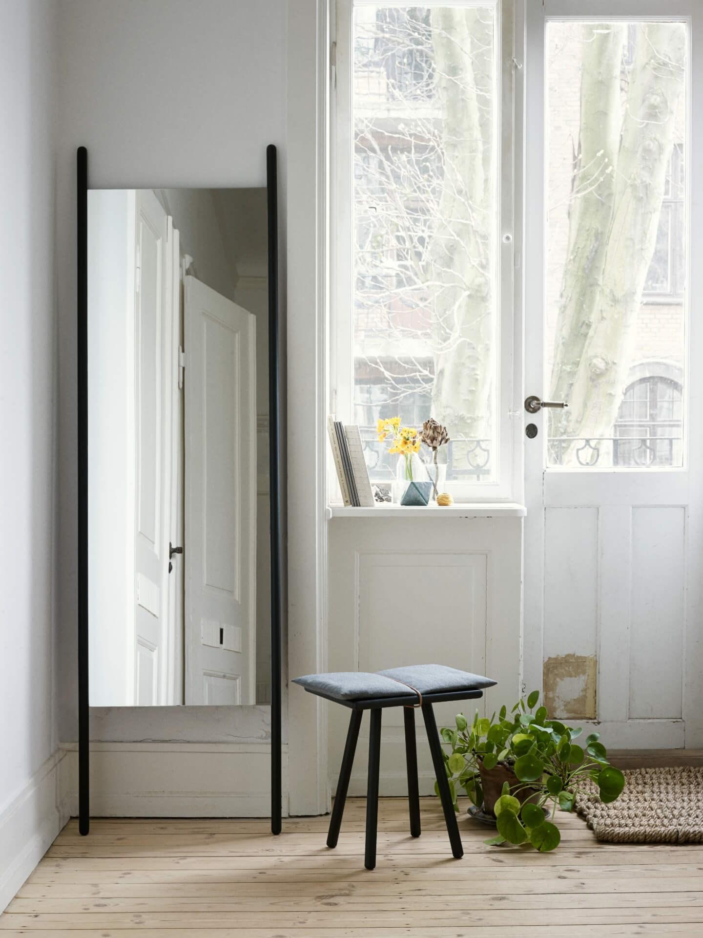 Miljøbilde speil i eik. Georg mirror fra Skagerak i sortmalt eik. Lyse vegger og grønn plante ved store vinduer.