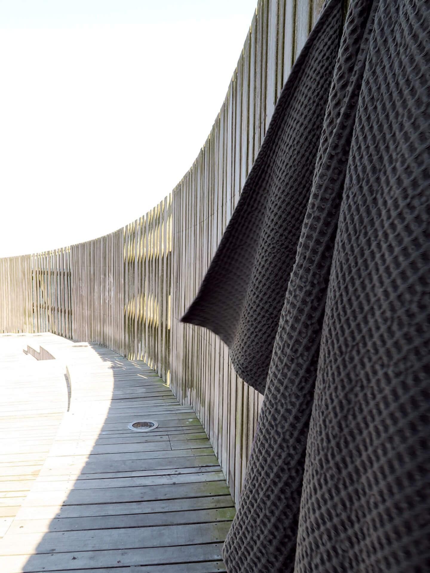 Miljøbilde badehåndklær bomull. Big waffle towel and blanket i grå fra The Organic Company. Hengende på vegg utendørs.