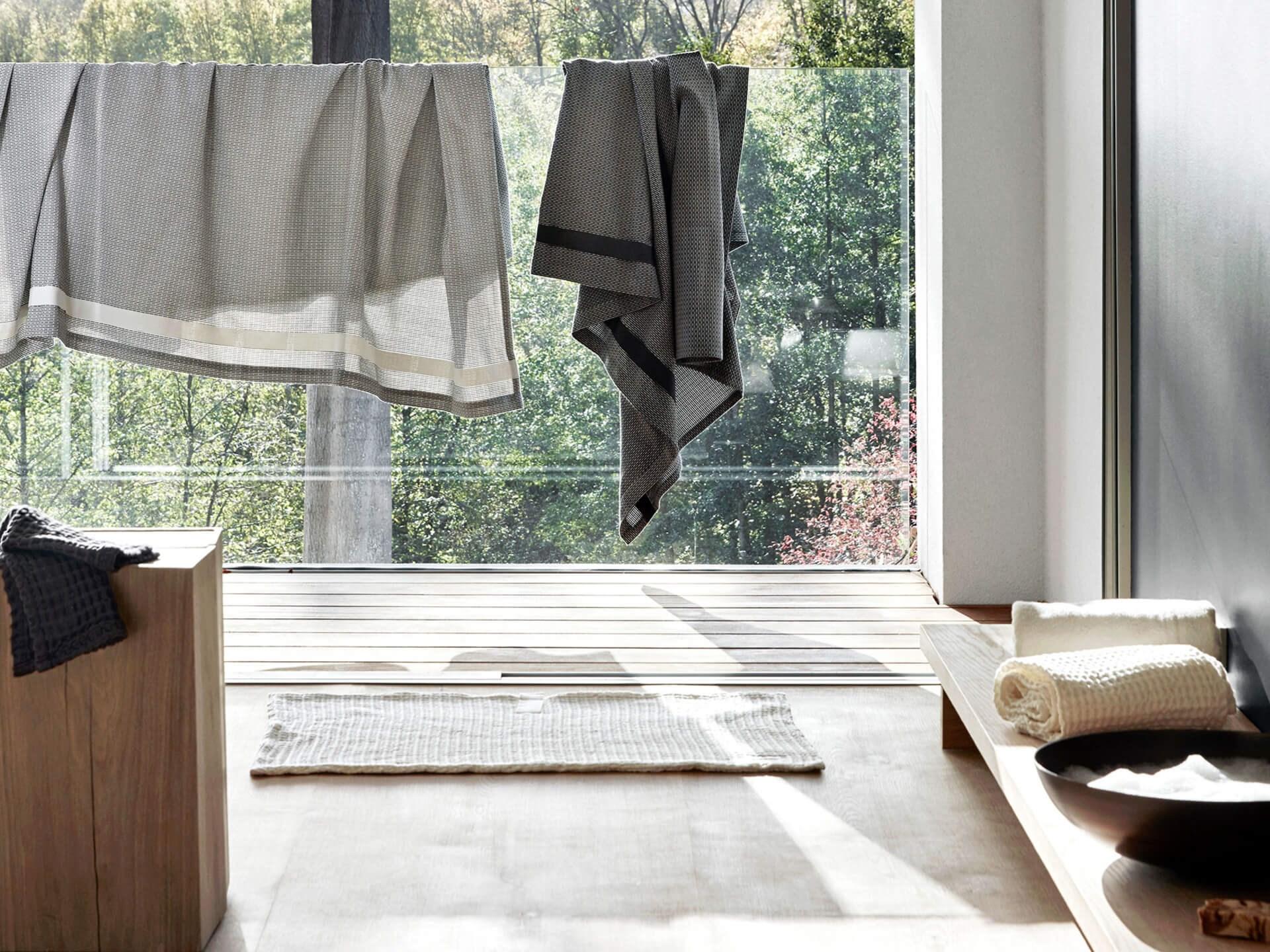 Miljøbilde badehåndkle i bomull. Wellness towel fra The Organic Company i morgning grey. Hengt på snor i japaninspirert bad.